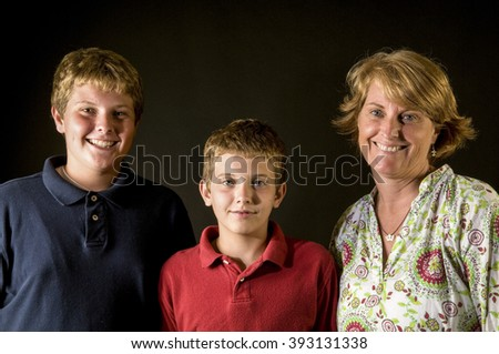 Single Mom with her teenage sons - happy family, studio portrait