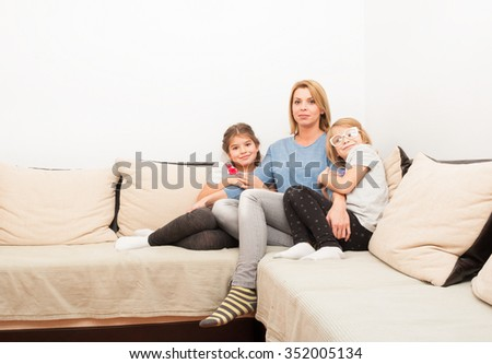 Single mother and two daughters bonding on at home on a couch or sofa - stock photo