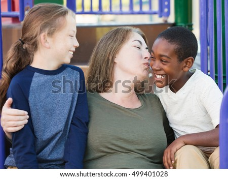 Single mother kissing her adopted son on cheek at park