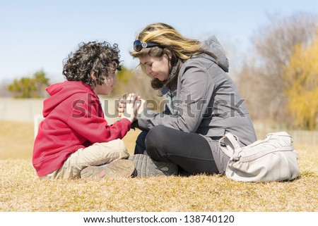Single mother teaching her son and glorifying God through prayer - stock photo