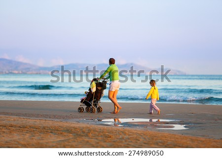 Single mother walking in silence with her daughter and baby, pushing a stroller on a sandy beach in late summer, enjoying the evening chill. Family vacation, traveling with children concept.  - stock photo