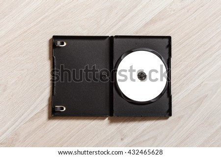 Single opened dvd cd disc cover case mockup. Template with plastic box and disc with white isolated free space for design. Mock up with black package for compact or dvd disc. Wooden table background - stock photo