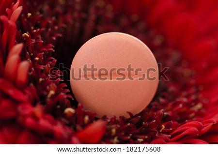 Single orange pill on red gerbera  - stock photo