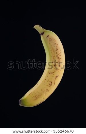 Single organic spotted banana isolated on black background