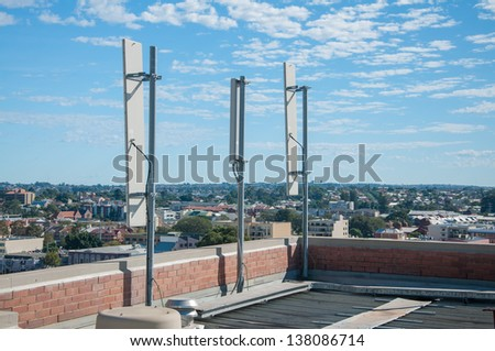Single panel antennas of cellular systems on a steel mast at the roof of building. - stock photo