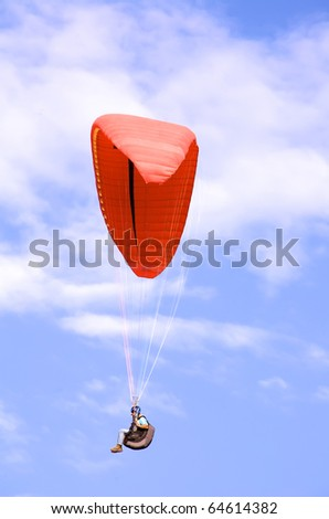 single paraglider with fluffy cloud background - stock photo