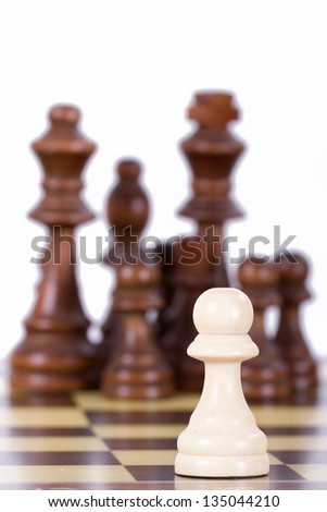 Single pawn against chess pieces on chess board, isolated on white background. - stock photo