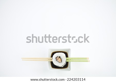 Single piece of maki sushi resting on chopsticks over dish of soy sauce, overhead view - stock photo