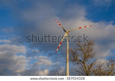 single pinwheel with clouds in a blue sky