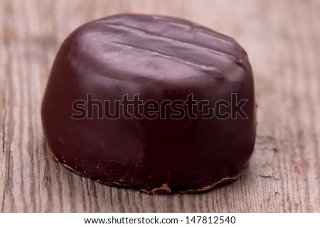 Single praline over wooden background - stock photo