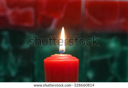 Single red candle burning with red and green holiday texture background - stock photo
