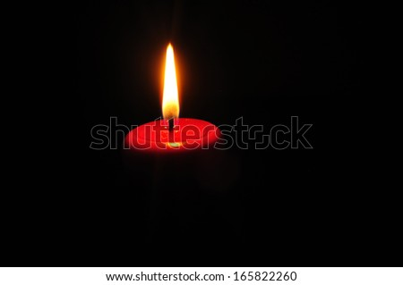 single red candle flaming in the dark