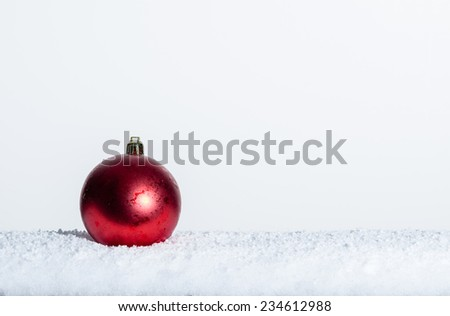 Single red Christmas ornament on snow room for text - stock photo