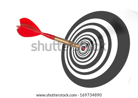 Single red dart penetrating the centre of a dart board scoring a bulls eye depicting achievement and accuracy - stock photo