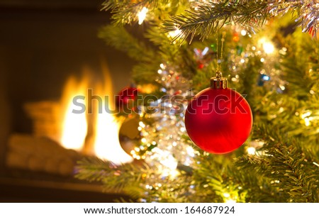 Single red holiday ornament hanging on tree with glowing fireplace in background  - stock photo