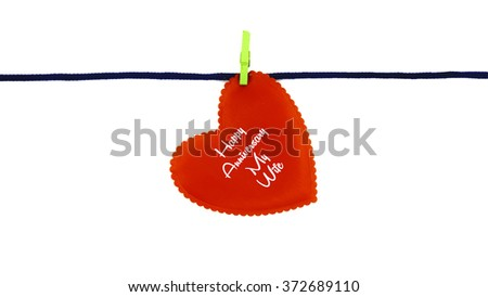 Single red love shape with text HAPPY ANNIVERSARY MY WIFE clipped on blue rope isolated on white background - stock photo
