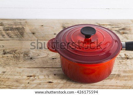 Single red saucepan on table - stock photo