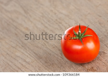 Single red tomato on a brown table