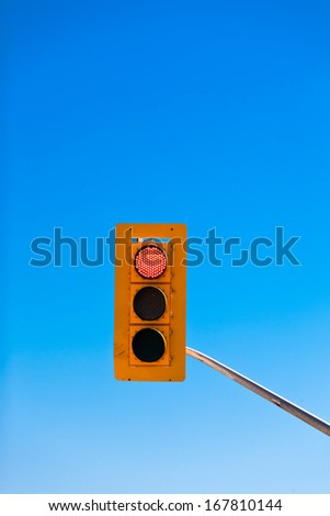 Single red traffic light demanding drivers to stop against blue sky with lots of copyspace - stock photo