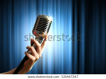 Single retro microphone against blue curtains closed on the background