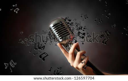 Single retro microphone against dark background with music notes - stock photo