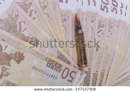 Single rifle bullet closeup with a pile of euro banknotes in the background - stock photo