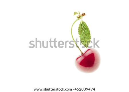 Single ripe cherry with a leaf on a white background. Isolated. Food background. Copy space.