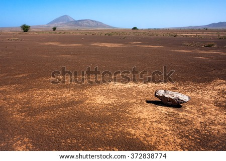 Single rock and empty flat desert fields in North of the Sal Island of Capo Verde. Volcanoes near Buracona bay. Martian like landscape - stock photo