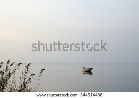 Single rowing boat in calm water a misty morning - stock photo