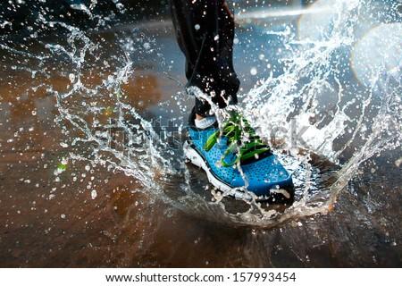 Single runner running in rain and making splash in puddle - stock photo