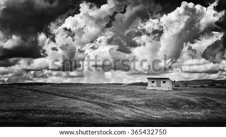Single rustic hut or home on a grass plain with a dramatic powerful cloud filled sky