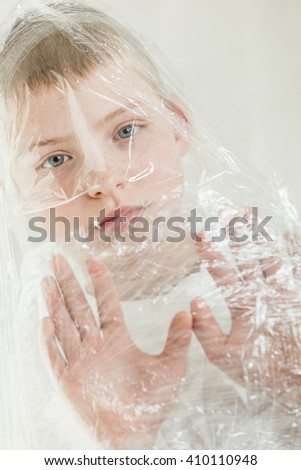 Single sad blond boy staring blankly with both hands and head wrapped in plastic turned to an angle - stock photo