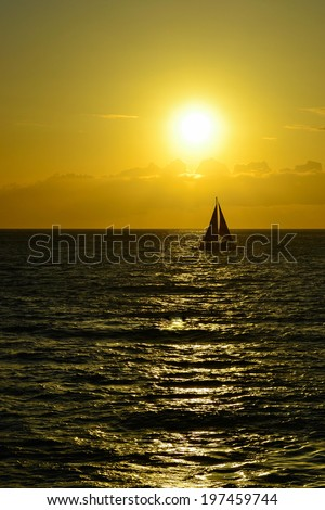 Single sailboat cruising on the ocean is silhouetted in front of the setting sun.