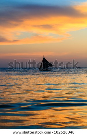 Single sailing boat with a tropical sunset reflected in a calm ocean - stock photo