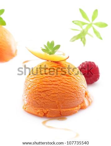 Single scoop of a colourful orange tropical mango icecream dessert on a white background - stock photo