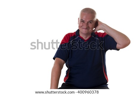 Single seated older man grins uncertainly and scratches behind his ear against a white background - stock photo