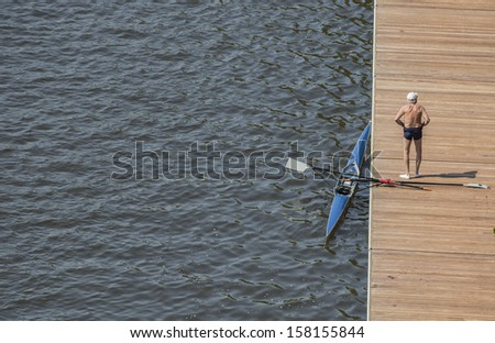 single senior standing backside by row boat on deck by river with hat - stock photo