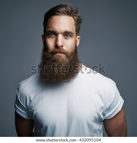 Single serious attractive young European man with muscular build and long fuzzy beard over gray background - stock photo