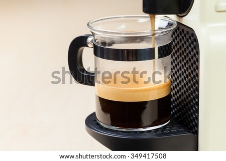 Single-serving coffee machine dispenses  espresso in a glass cup
