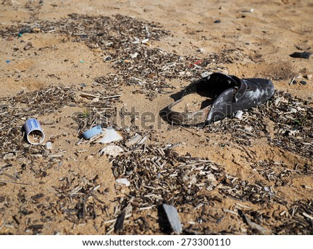 Single shoe with other garbage on the beach - stock photo