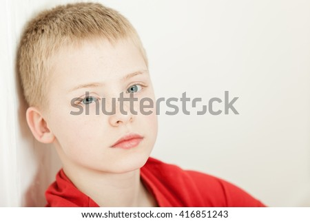 Single sick little blond boy wearing red shirt with tired expression sitting back against wall with copy space