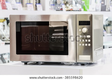 single silver metallic microwave oven at retail store shelf, defocused background - stock photo