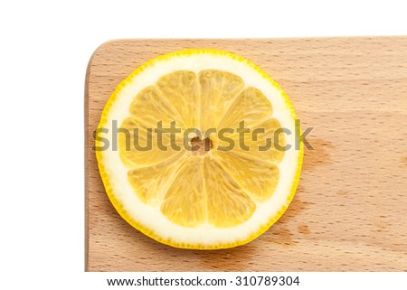 Single slice of lemon on a cutting board, simple and minimalist - stock photo