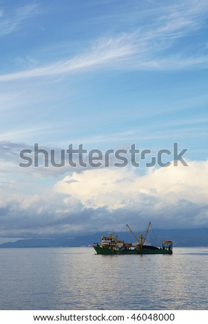 Single small fishing trawler leaving the harbor into the the blue Aegean sea to go fishing on a cloudy winter's day. - stock photo