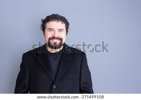 Single smiling handsome dark haired and bearded middle aged man wearing black shirt and blazer over gray background with copy space - stock photo
