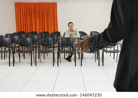 Single smiling man applauding seminar in conference room - stock photo