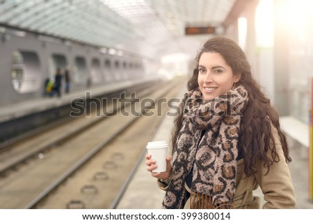 Single smiling woman in light brown winter coat and coffee cup in hand while standing at commuter train station platform - stock photo