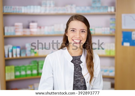 Single smiling young adult female pharmacist in white lab jacket in front of shelf of obscured medication