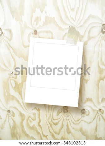 Single square empty instant photo frame with scotch tape on light brown wooden board background