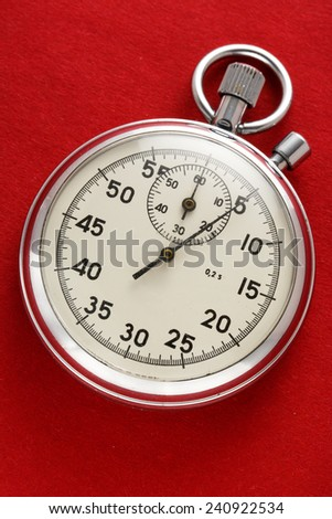 Single stopwatch closeup on red paper background